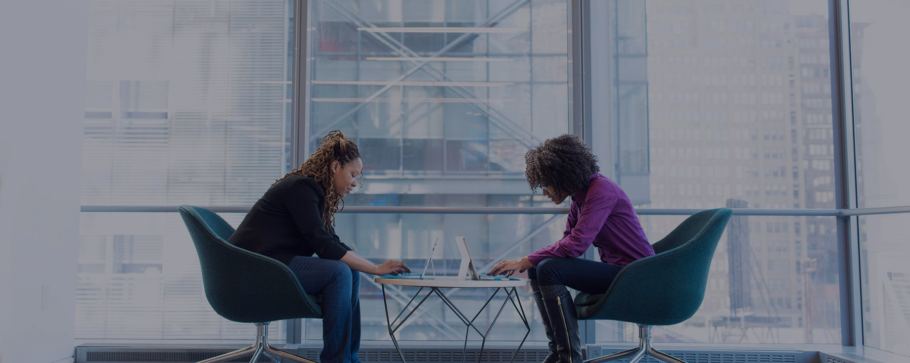 Two women facing each other working on laptops in front of large glass window.