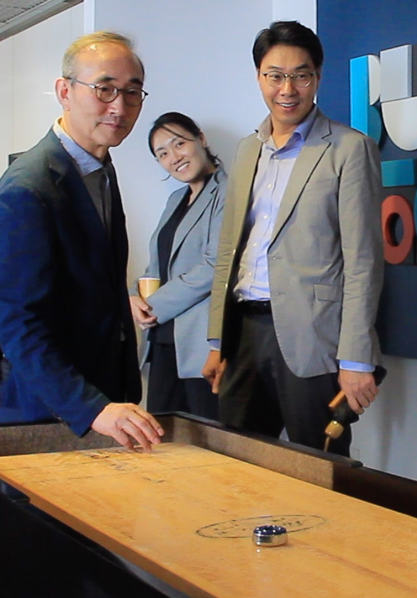 Three men and one woman in dress jackets playing shuffleboard.