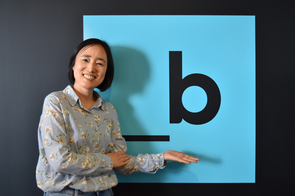 Woman smiling in front of large cyan  _b logo on wall.
