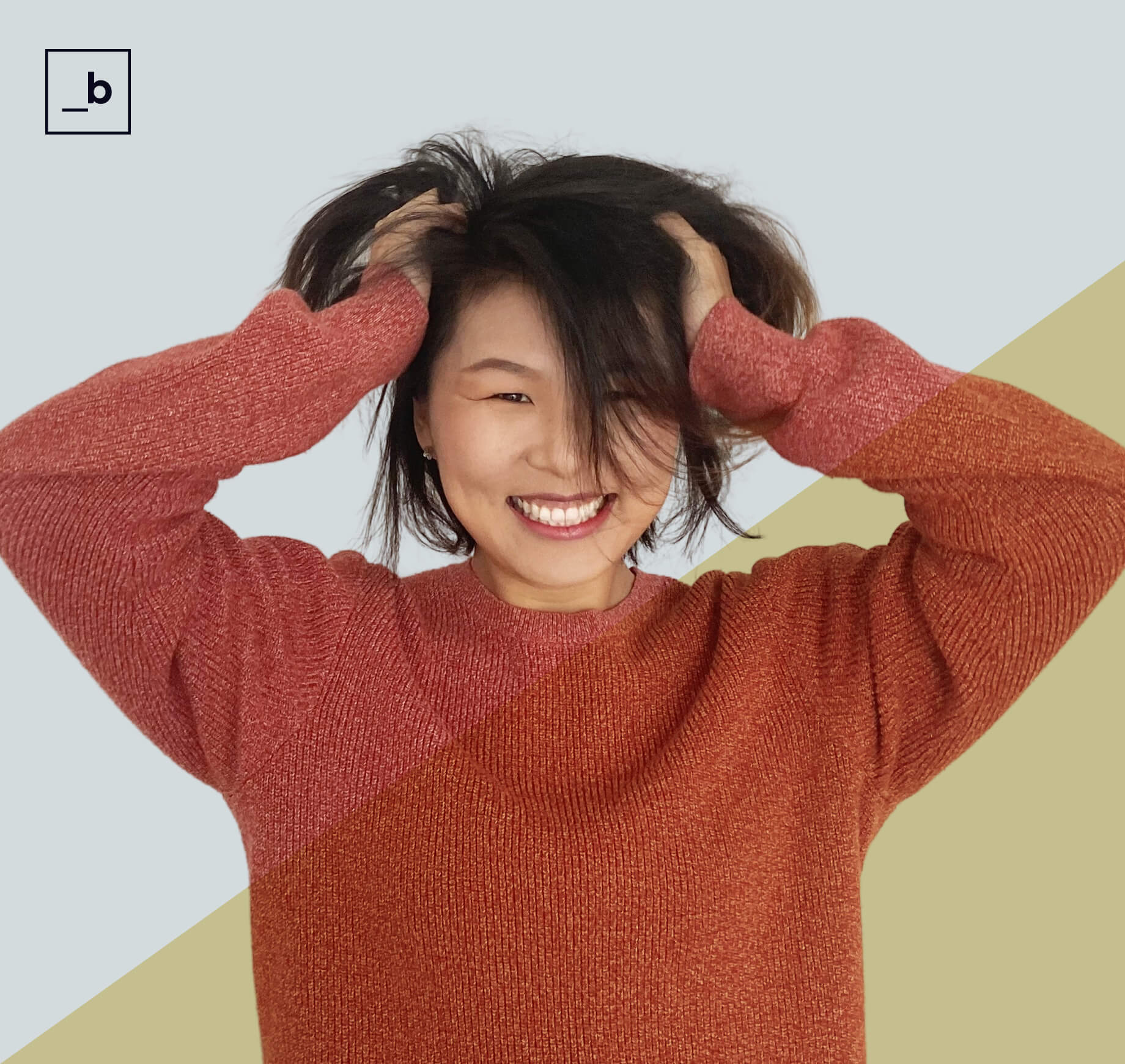 Woman in red sweater looking forward smiling, with her hands in her hair.