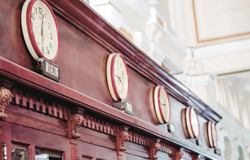 Lineup of clocks against a decorative wooden frame.