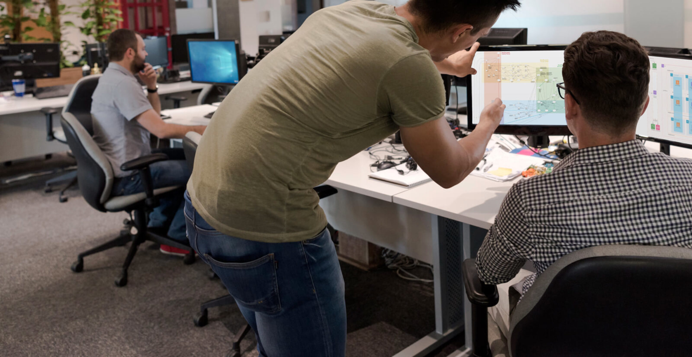 two people collaborating at desktop computer screens.