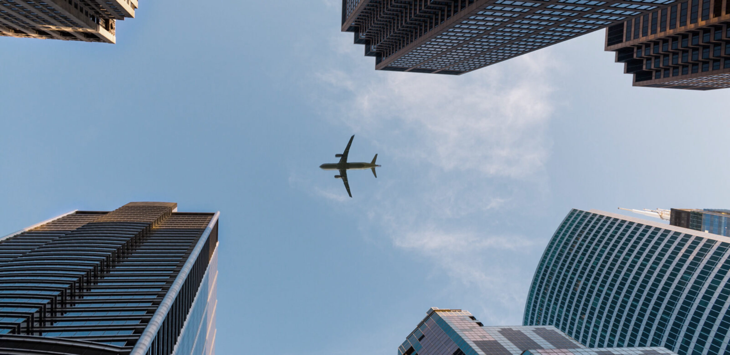 Looking straight up between buildings to see an airplane flying overhead.