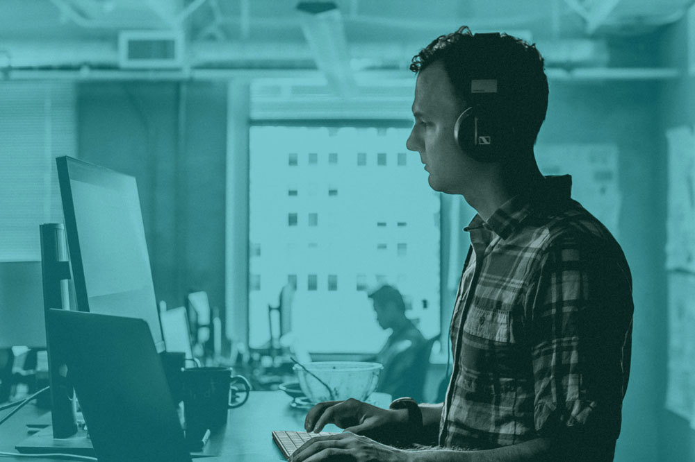 Cyan duotone man standing at computer wearing headphones.