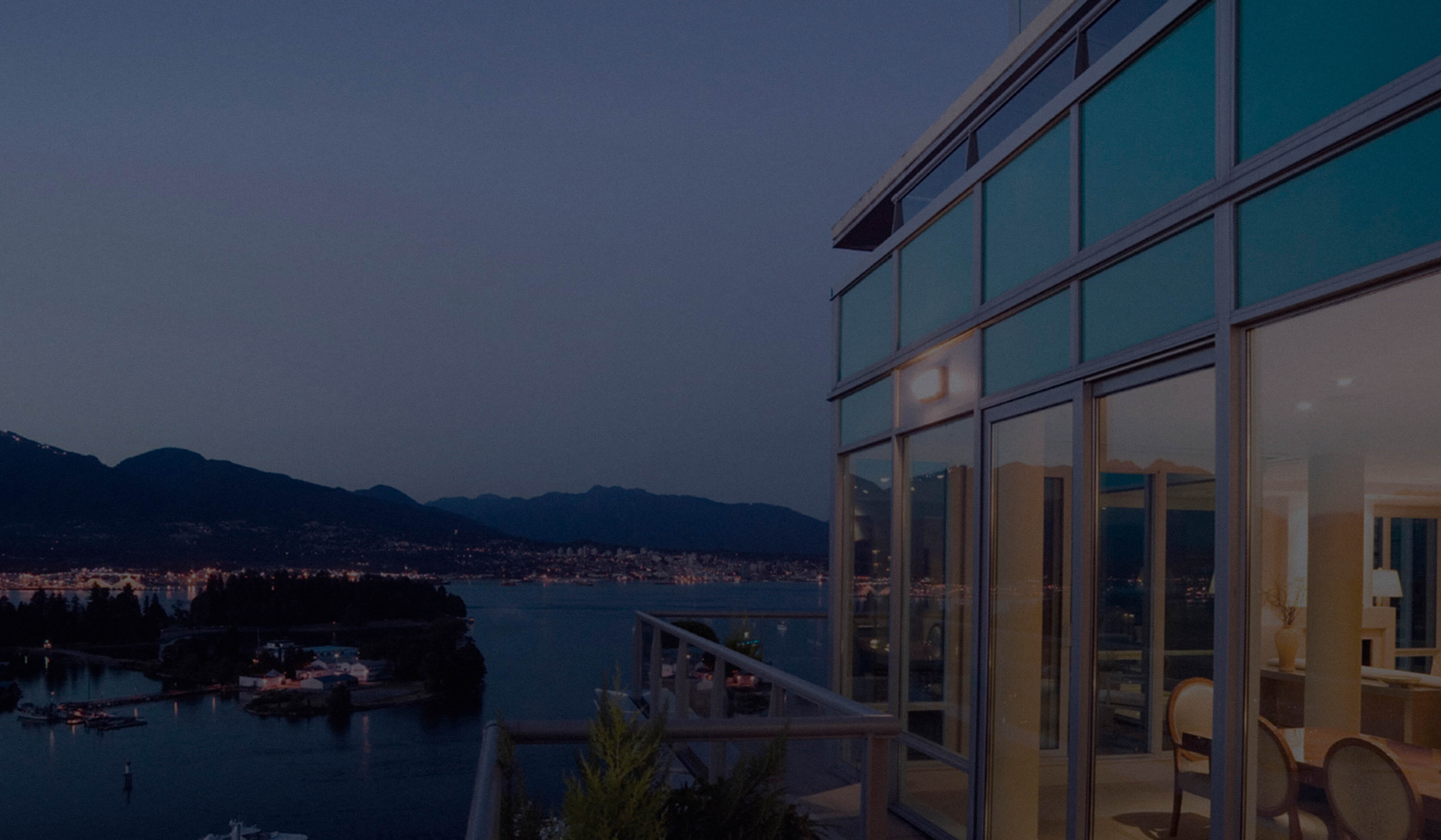 Deck of a modern high-rise building overlooking marina, harbor, and mountains.