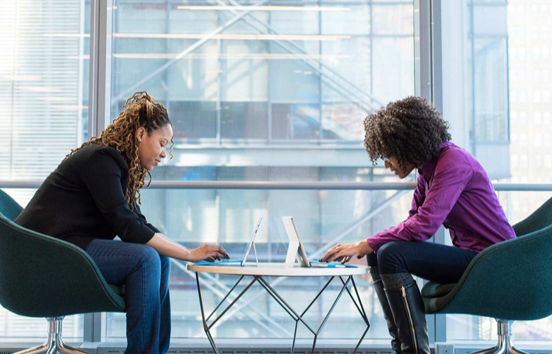 Two woman facing each other working on laptops in front of huge glass window.