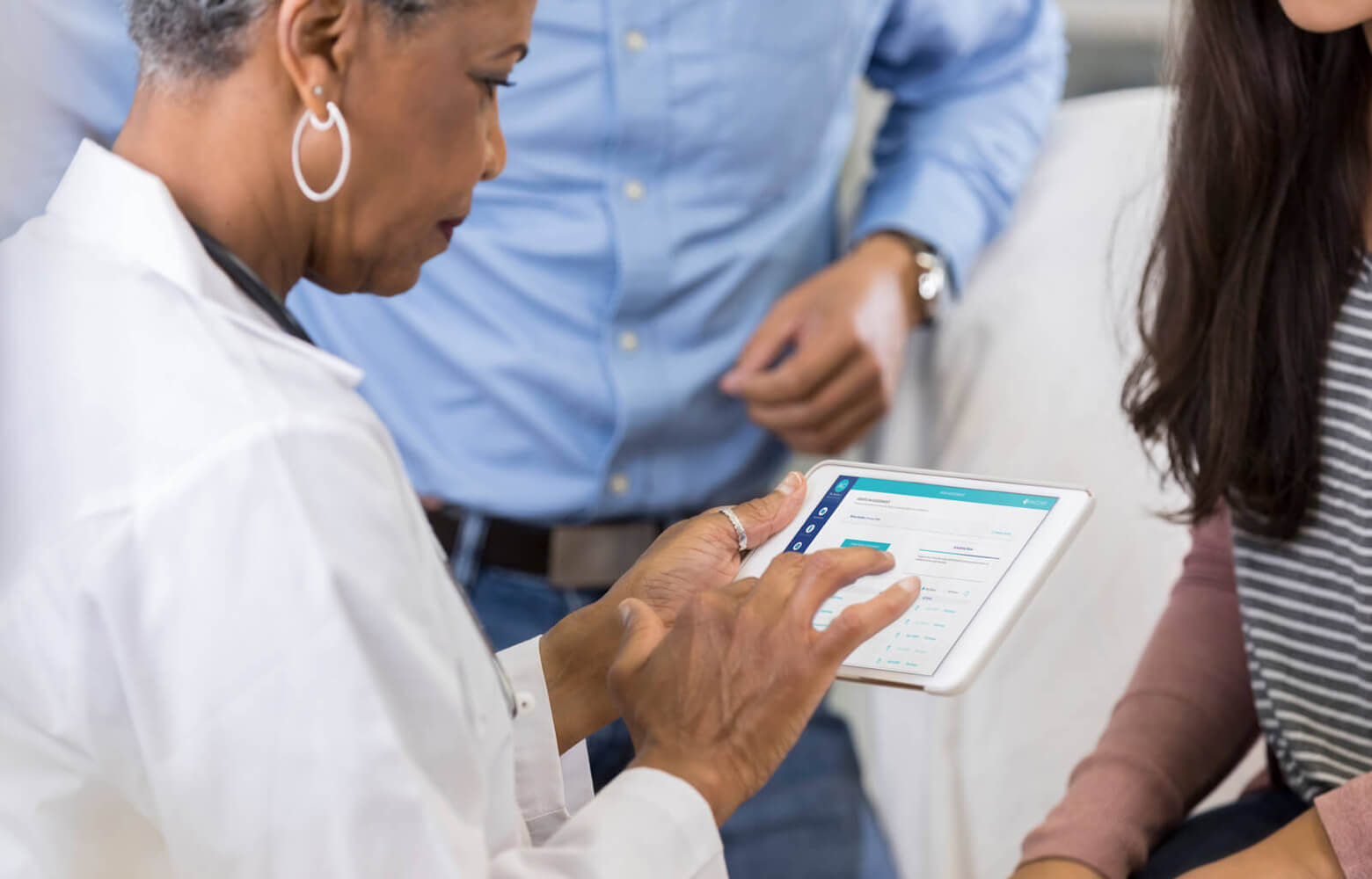 Doctor taking notes on digital tablet while meeting with two patients.