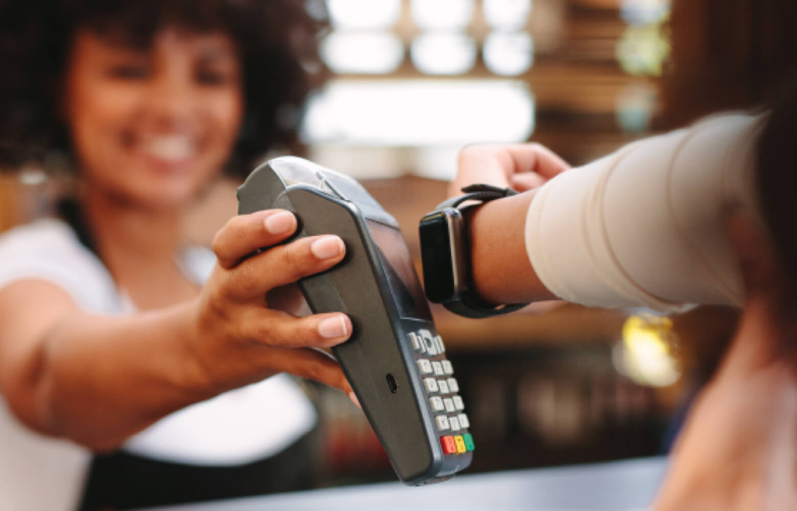 Store clerk holding payment terminal for a woman to tap with her smart watch for payment.